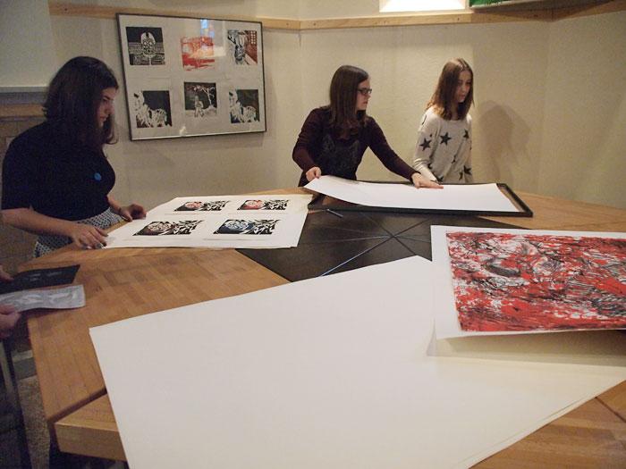 """Schülerinnen bereiten Bilder für die Ausstellung """"KriegsVerklärung"""" vor"""